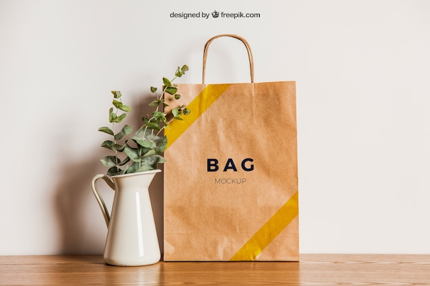 Paper bag mockup next to flower pot Free Psd