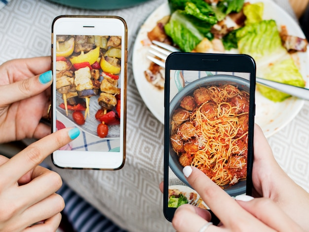 People sharing food photos on mobile phone Premium Psd