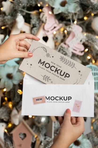 Persona in possesso di carta con busta accanto alle decorazioni natalizie Psd Gratuite