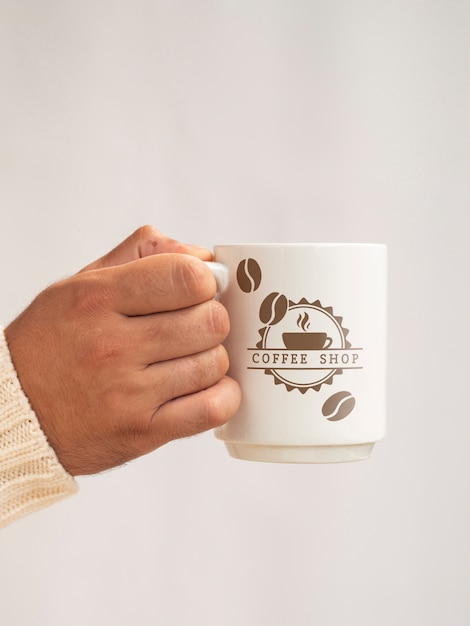 Person holding a cup of coffee mock-up Free Psd