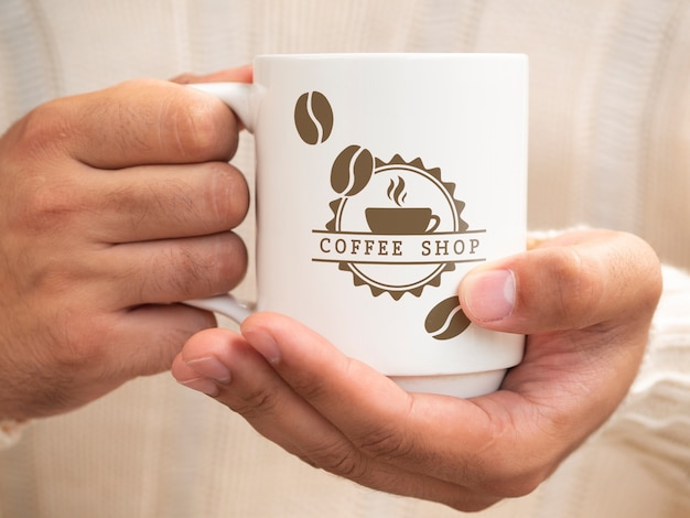 Person holding a cup of coffee Premium Psd