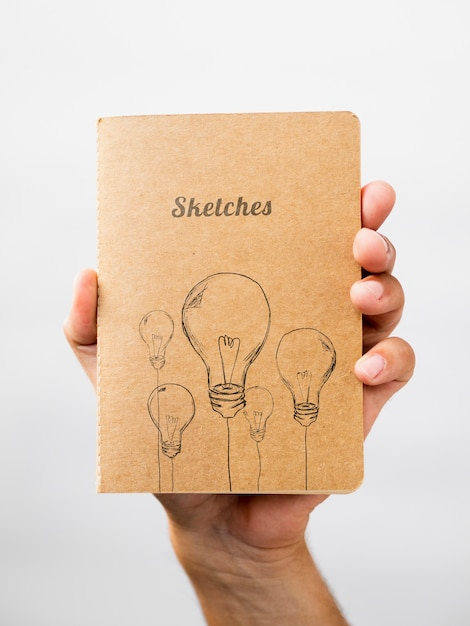 Person holding a sketch book Free Psd