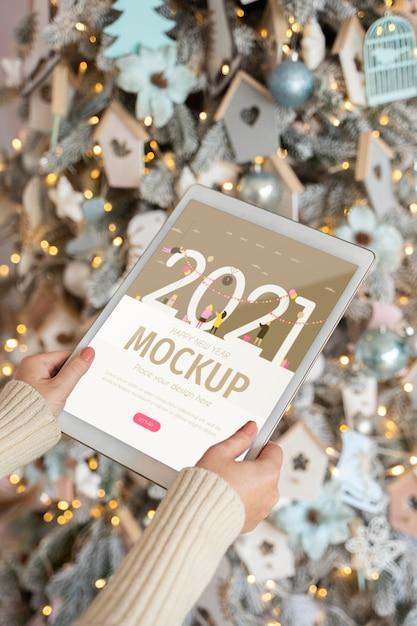 Человек, держащий планшет с новым годом перед рождественскими украшениями Premium Psd