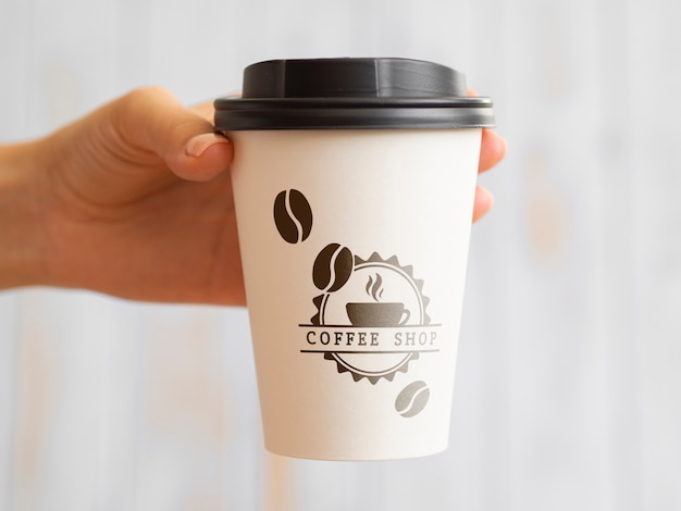 Person holding up a coffee paper cup Free Psd