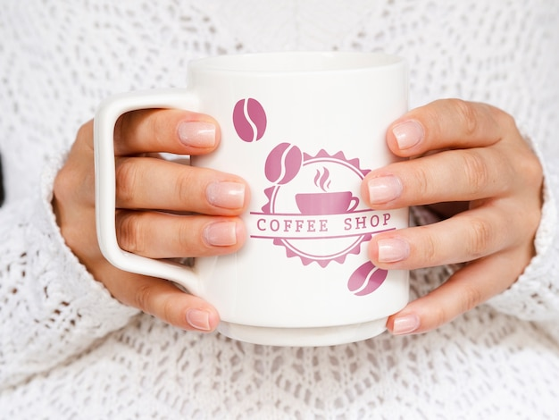 Person holding white coffee mug mock-up Free Psd