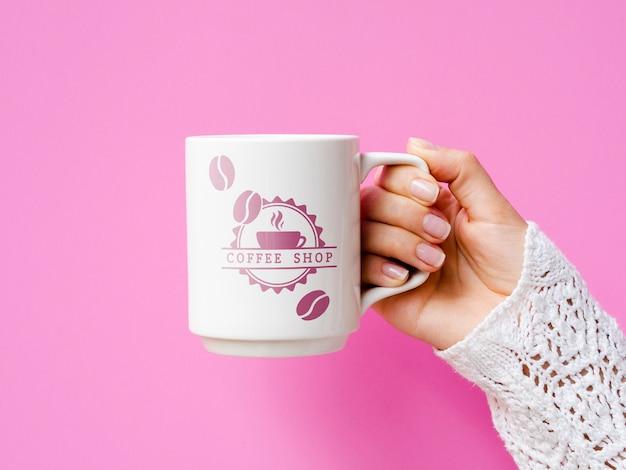 Person holding white mug mock-up on pink background Free Psd