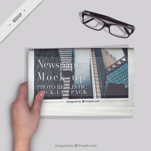 Person reading a newspaper with a glasses on the desktop Free Psd