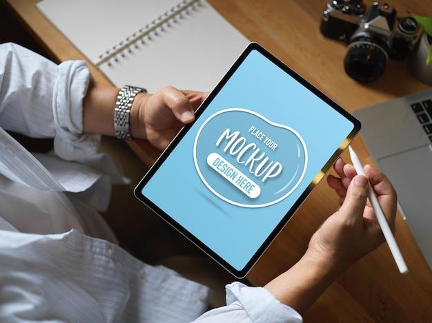 Человек, работающий с макетом цифрового планшета на рабочем столе в офисе Premium Psd