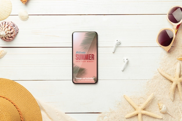 Phone mockup and beach accessories on white wood table. Premium Psd