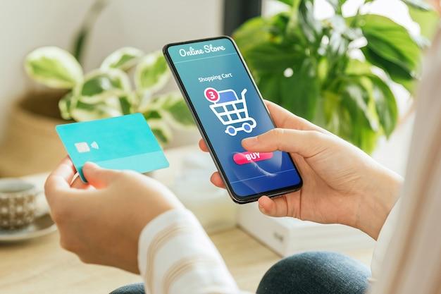 Макет телефона, который держит женщина, оплачивающая онлайн-заказ из дома Premium Psd