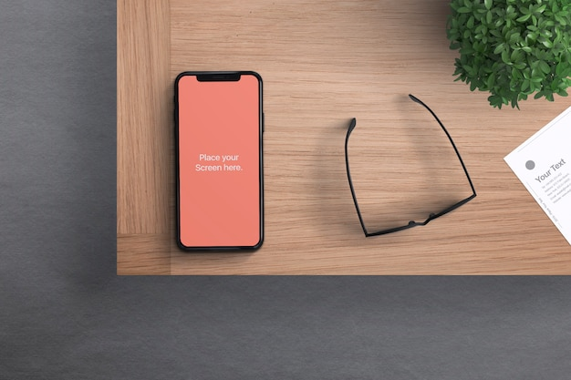 Phone with glasses on desk mockup Premium Psd