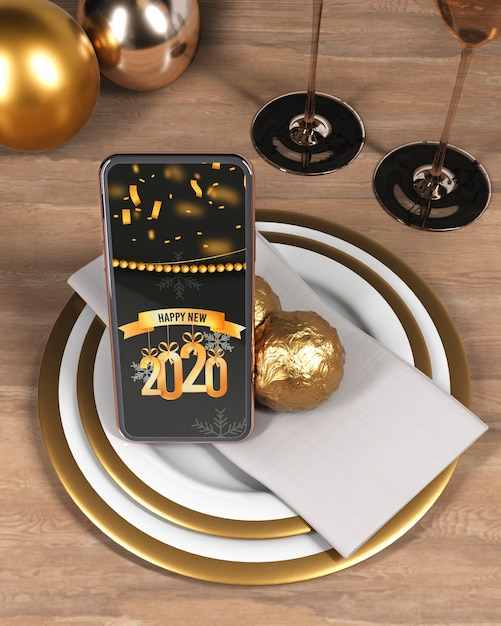 Phone with message for new year on plate Free Psd