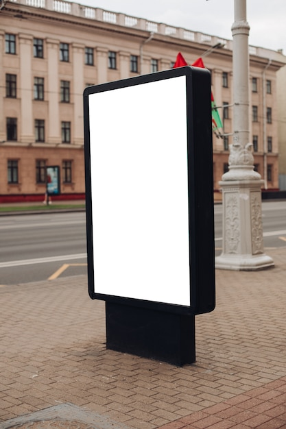 Photo of a large billboard that stands on the street, where many people walk Premium Psd