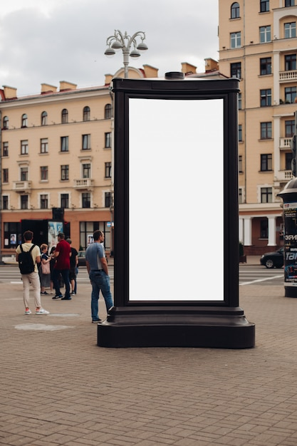 Photo of a large billboard that stands on the street, where many people walk Free Psd