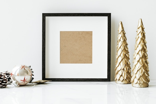 Picture frame on a table with golden christmas tree Free Psd