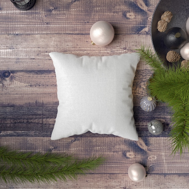 Pillow on a wooden table surrounded by baubles, pines and fir Free Psd