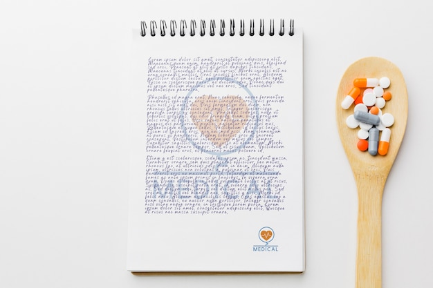 Pills on wooden spoon with notepad Free Psd