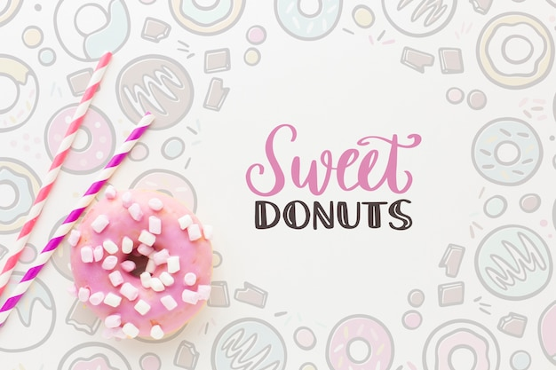 Pink donut with sweets and mock up Free Psd