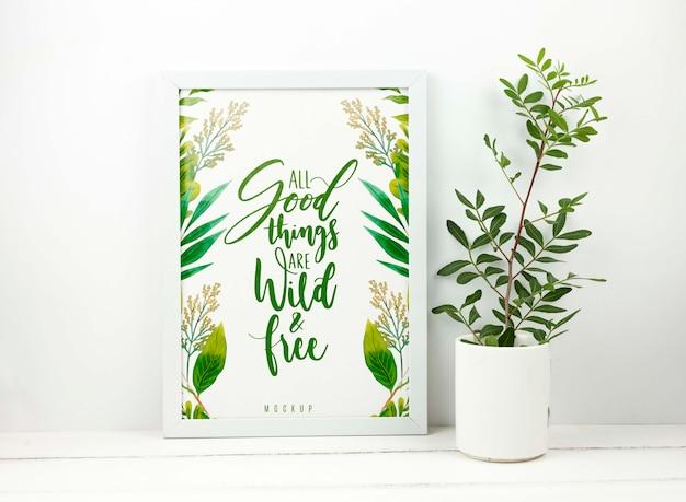 Plant next to frame mockup Free Psd