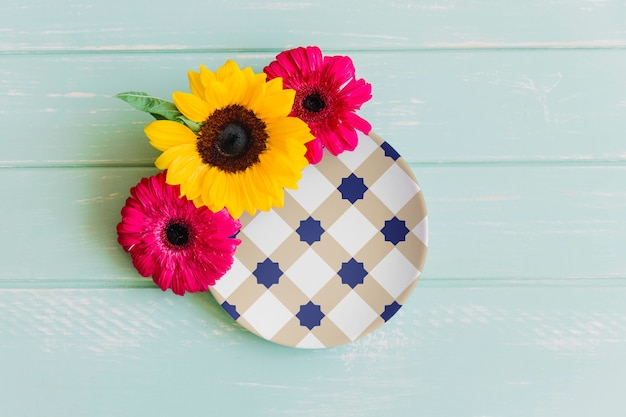 Plate mockup with three flowers Free Psd