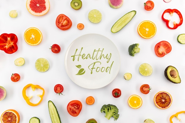 Plate surrounded by veggies and fruit top view Free Psd