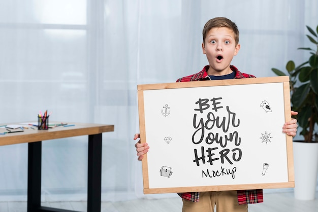 Portrait of child holding mock-up sign Free Psd