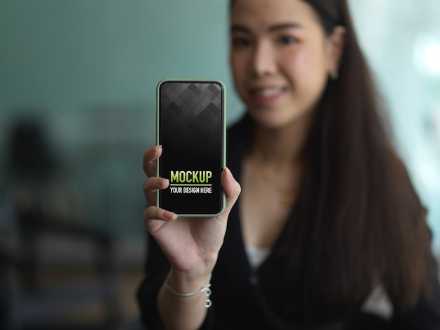 Portrait of female in black suit hand holding smartphone to show mock up screen Premium Psd