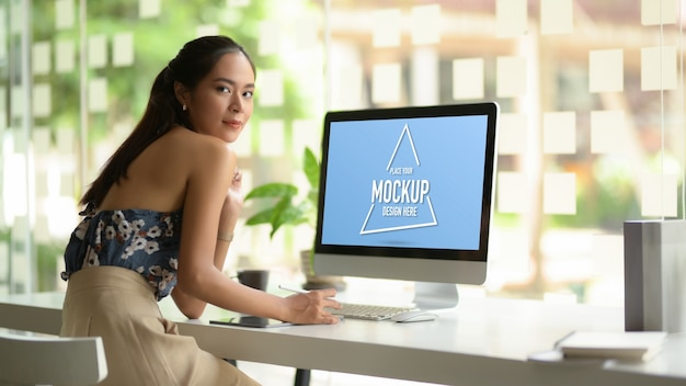 Portrait of female fashion designer looking into camera and smiling while working on computer table Premium Psd