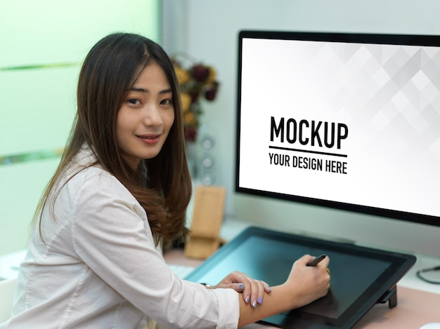 Portrait of female office worker working with drawing tablet and computer mockup Premium Psd