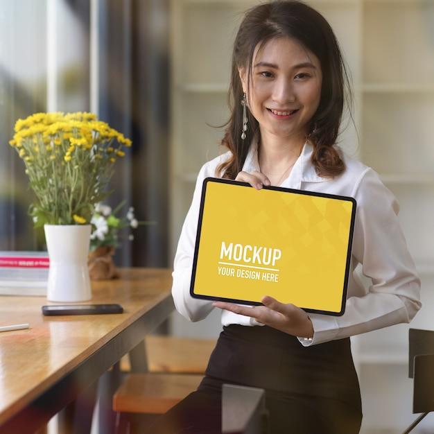 Portrait of female showing digital tablet mockup Premium Psd