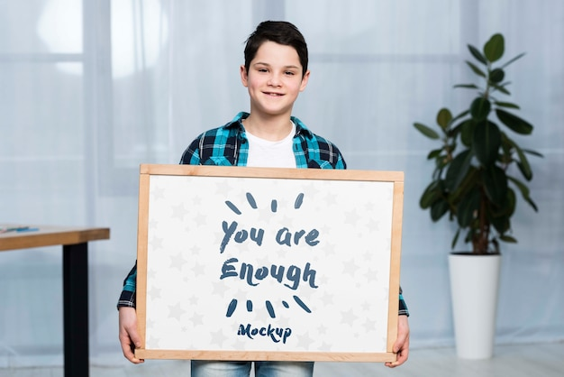 Portrait of positive child holding mock-up sign Free Psd