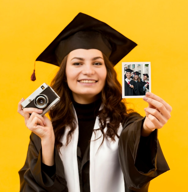 Portrait of student holding instant photo Free Psd