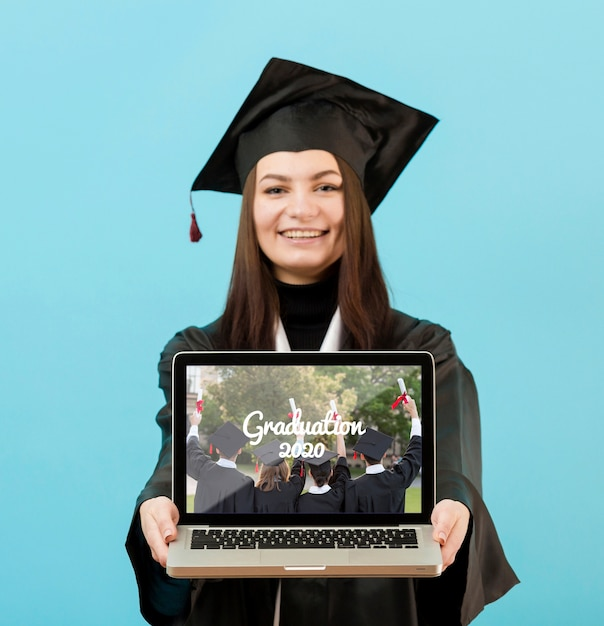 Portrait of student holding laptop with mock-up Free Psd