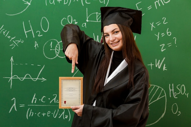 Portrait of student pointing at diploma Free Psd