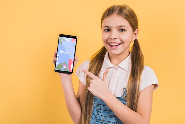 Portrait of young girl holding mobile phone Free Psd