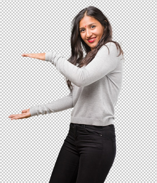 Portrait of young indian woman holding something with hands, showing a product Premium Psd