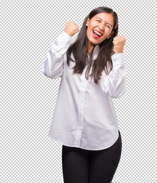 Portrait of a young indian woman very happy and excited, raising arms, celebrating a victory or success, winning the lottery Premium Psd