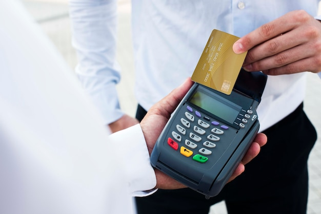 Pos terminal and credit card with businessmen outdoors Free Psd