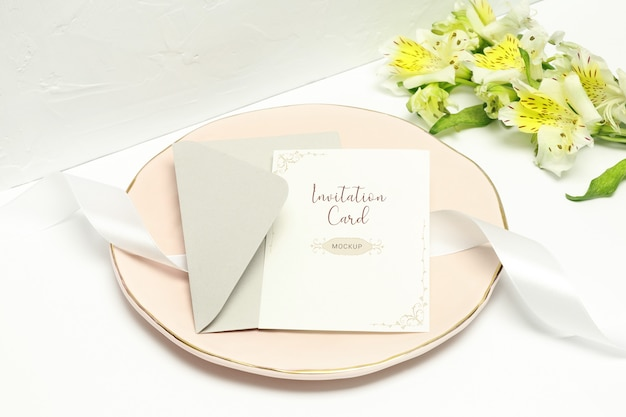 Postcard on pink plate with white ribbon, grey envelope and white flowers Premium Psd
