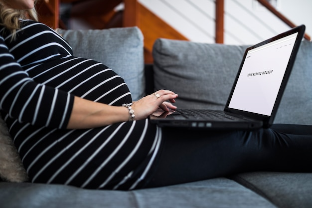 Pregnant woman on couch using computer Free Psd