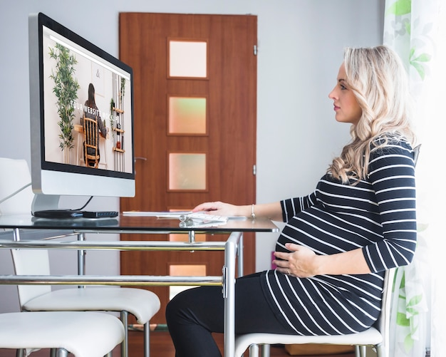 Pregnant woman using computer Free Psd