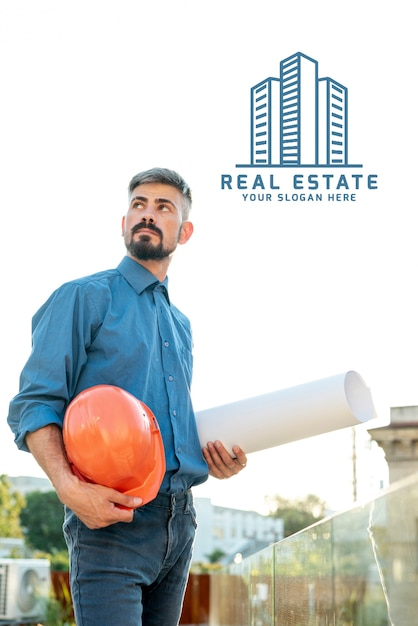Real estate agent holding plans for the new building Free Psd