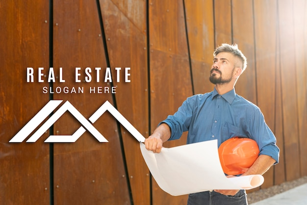 Real estate agent looking up and holding plans Free Psd