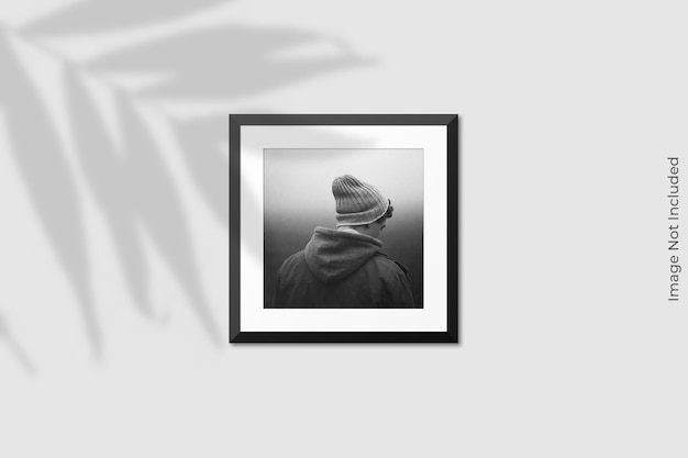 Realistic square frame mockup hanging on wall with shadow overlay Premium Psd