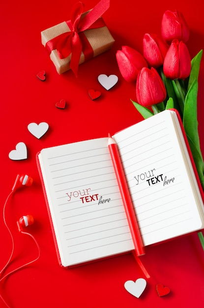 Red notebook with bouquet of tulips, gift box, wooden hearts, pencil and headphones. Premium Psd