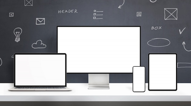 Responsive display devices on web designer desk mockup. office desk concept with isolated screens on computer display, laptop, phone and tablet. web design elements drawings in background Premium Psd