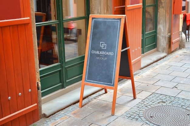 Restaurant chalkboard mockup on city street Premium Psd