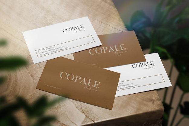 Чистый минимальный макет визитной карточки на деревянный стол и rianbow свет с листьями. Premium Psd