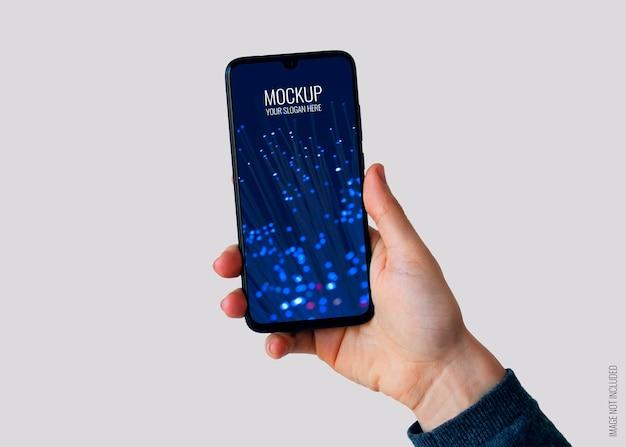 スマートフォンのモックアップを持っている右手 無料 Psd