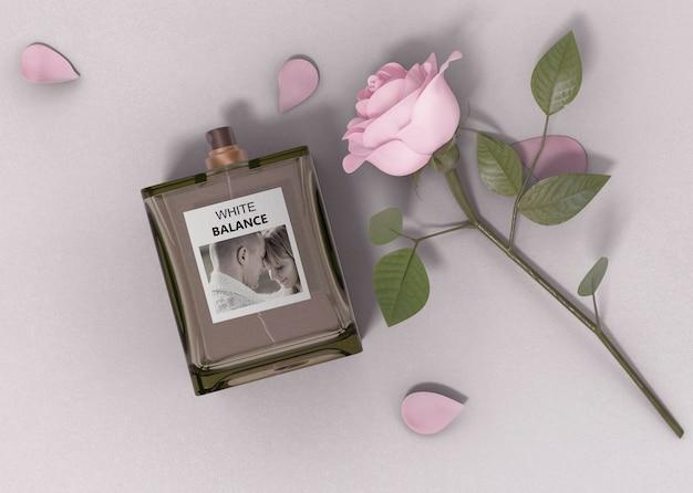 Роза рядом с флаконом духов на столе Premium Psd